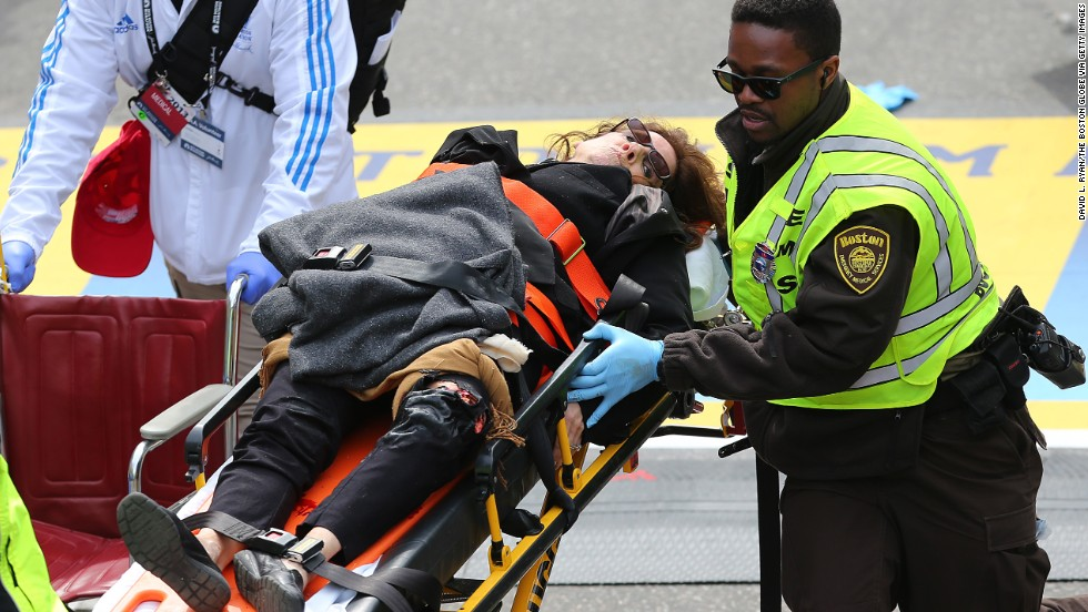 An injured woman is carried away on a stretcher.