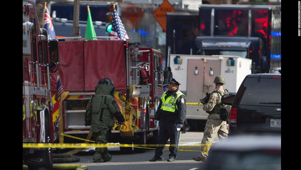 Bomb squad officials check a possible suspicious device near the scene of the blasts.