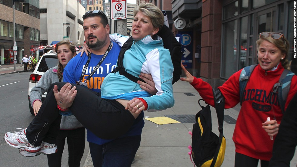 "Former New England Patriots <a href=""http://bleacherreport.com/articles/1606043-former-new-england-patriot-joe-andruzzi-assists-survivors-at-boston-marathon"" target=""_blank"">offensive lineman Joe Andruzzi</a> carries a woman from the scene."