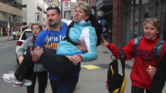 Former New England Patriots offensive lineman Joe Andruzzi carries a woman from the scene.