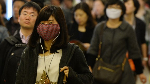 Pedestrians in Shanghai wear face masks to protect themselves from  the H7N9 bird flu virus on Tuesday, April 16.