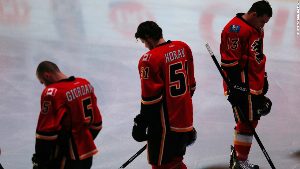 Members of the Calgary Flames observe a moment of silence before the start of their National Hockey League game against the Minnesota Wild in Calgary, Alberta, on Monday, April 15.