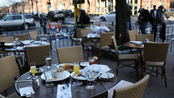 The unfinished meals of fleeing customers are left on tables at an outdoor restaurant in Boston on April 16.