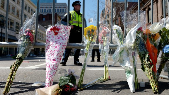 Flowers rest against a police barricade down the street from the Boston Marathon