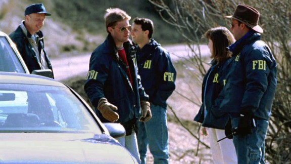 """Three people were killed and 23 others were wounded after a string of mail bombings carried out by Ted Kaczynski, aka """"The Unabomber,"""" from 1978 to 1995. Here, FBI agents guard the entrance to Kaczynski's property in Lincoln, Montana, on April 5, 1996. In May 1998, Kaczynski received eight life sentences for his crimes."""
