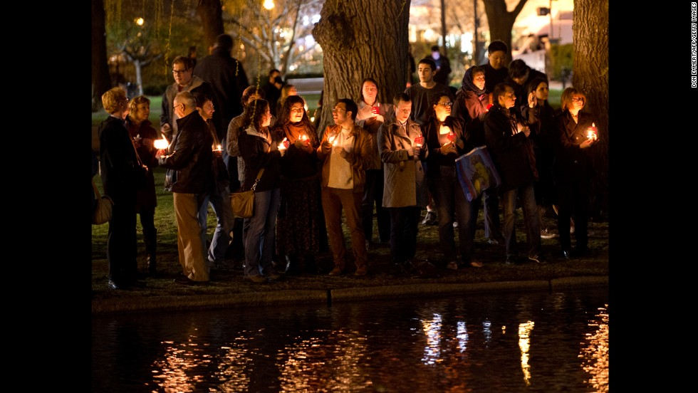 Mourners gather on the edge of the pond for a candlelight vigil in Boston on April 16, 2013.