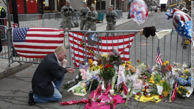 BOSTON, MA - APRIL 16: Mike Vitale, who lives in the Boston area, prays beside flowers and remembrances for victims of the bombing of the Boston Marathon at a roadblock at the end of Boylston Street, on April 16, 2013 in Boston, Massachusetts. Two bombs exploded near the finish line of the marathon the day before, killing some and injuring more than 100 people.(Photo by Melanie Stetson Freeman/The Christian Science Monitor via Getty Images)