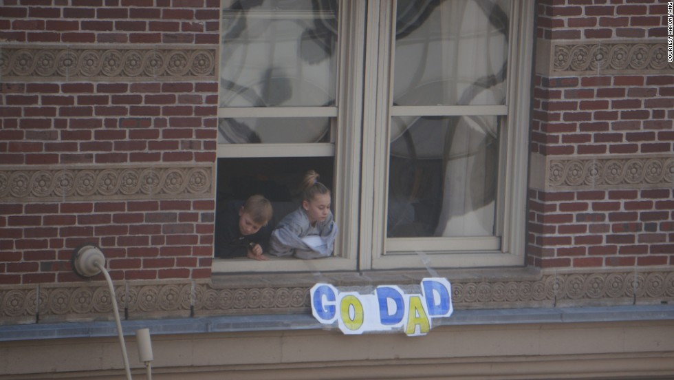 Children watch the race from a window.