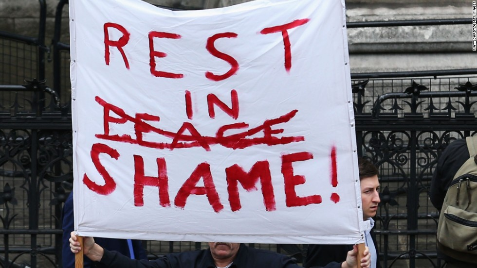 A protester holds a banner at the Church of St. Clement Danes in London.