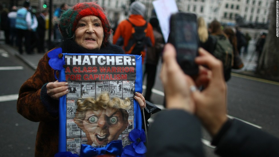 Protester Mary MacMillan holds a sign of protest at Trafalgar Square ahead of the funeral procession.