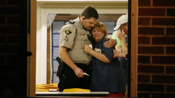 A sheriff's deputy comforts a woman at a command post.