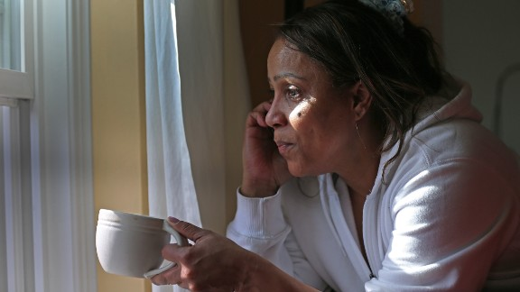 Katia Costa looks out her window as police continue the manhunt on Nichols Avenue in Watertown on Friday.