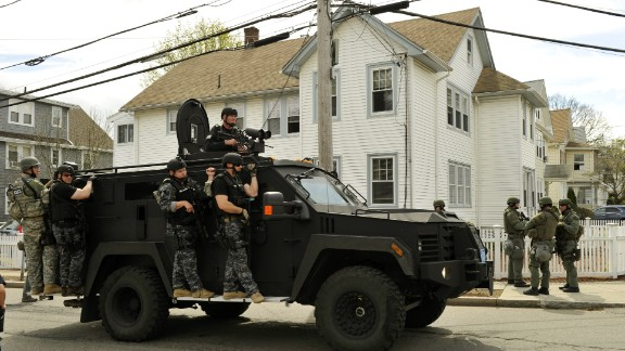 A police SWAT team searches houses on April 19 for the second suspect.