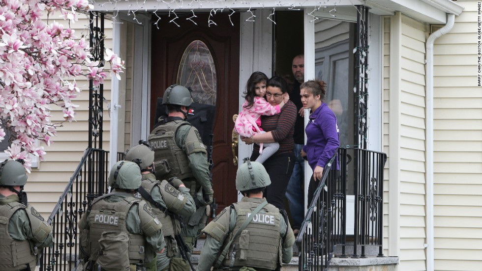 SWAT teams prepare to enter a home as they continue the door-to-door search.