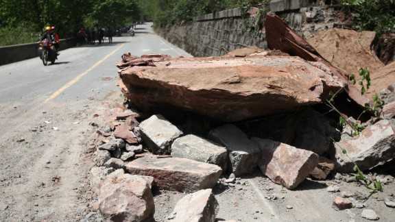 Huge rocks lie on a road in Longmen on Saturday.