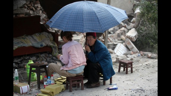 A girl gives offerings to the dead by the side of ruins in Longmen on Saturday.
