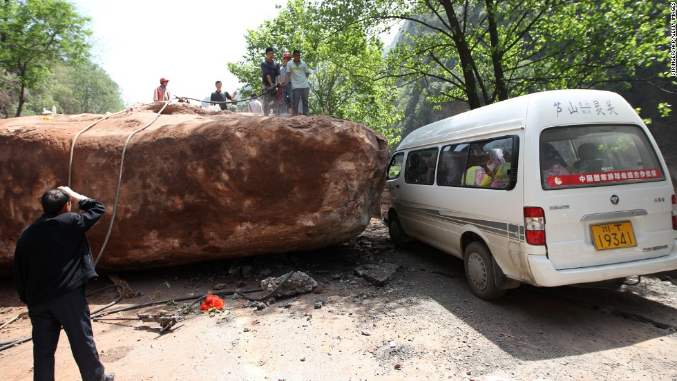 People attempt to move a huge rock blocking the road to Longmen township on Saturday.