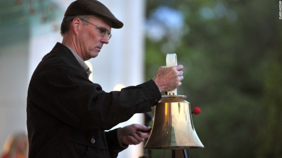 A man rings a bell at the vigil in Huntsville.