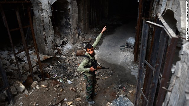 A Syrian rebel fighter points to destruction in the Umayyad Mosque complex in the old part of Syria's northern city of Aleppo on April 16, 2013. After nine months of fighting that has devastated many districts in Aleppo, rebels now control more than half of the city. AFP PHOTO / DIMITAR DILKOFF (Photo credit should read DIMITAR DILKOFF/AFP/Getty Images)