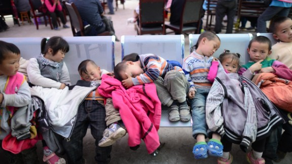 Displaced children rest at an evacuation shelter in Baosheng township on Saturday.