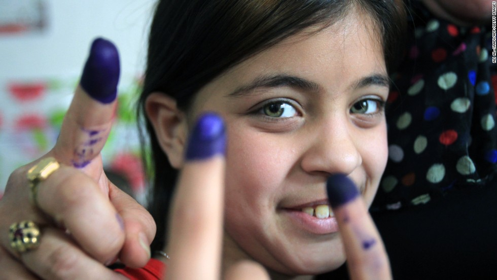 An Iraqi girl is surrounded by the ink-stained fingers of women after they voted on Saturday.