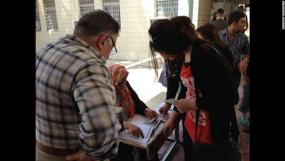 Iraqis line up to cast their vote as a poll worker checks their identification against voter records. According to Iraq's Electoral Commission, voter turnout across the country is around 50%.