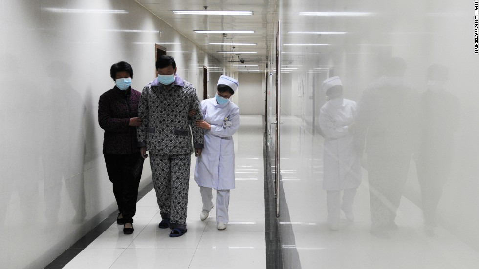 An H7N9 bird flu patient walks in the corridor of a hospital after his recovery and approval for discharge in Bozhou, in central China's Anhui Province, on Friday, April 19.