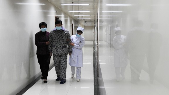 An H7N9 bird flu patient walks in the corridor of a hospital after his recovery and approval for discharge in Bozhou, in central China