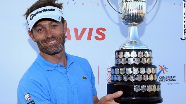 French golfer Raphael Jacquelin poses with the winner's trophy after a marathon playoff at the Open de Espana.