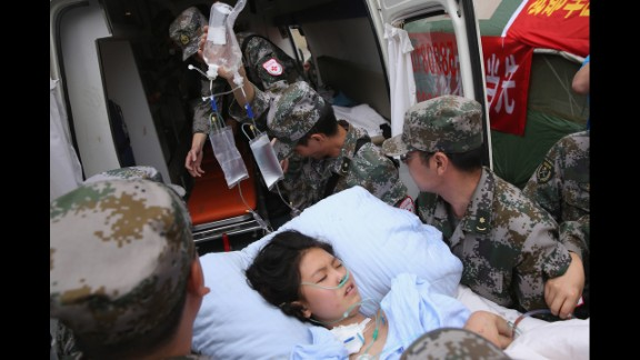 Military medical officers carry a patient to an ambulance at the hospital in Ya