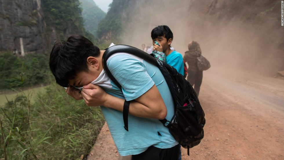 People cover their faces as rocks fall from mountains on their way home to Ya'an on Sunday.