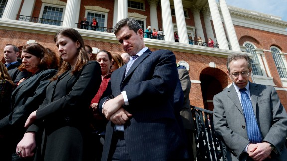 State employees pause for a moment of silence on the steps of the Massachusetts State House.