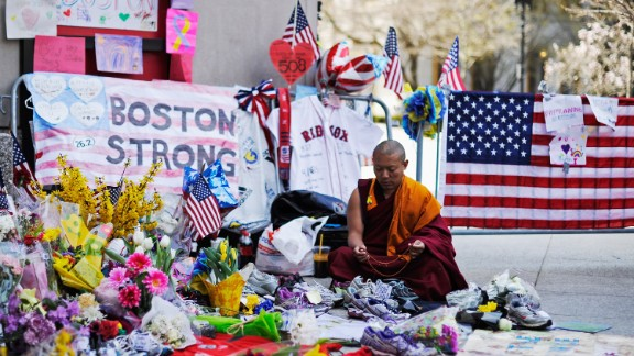 A Buddhist sits at a memorial near the marathon finish line during a moment of silence on April 22, 2013.