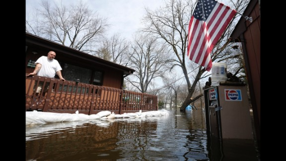 Joe Kozlowski surveys his flooded property from his porch in Fox Lake on April 22. Downpours have created flooding concerns for rivers in Illinois, Missouri, Iowa, Indiana and Michigan, the National Weather Service said.