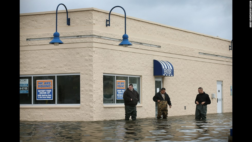 Workers inspect flood damage to a building in Des Plaines on April 19. At least six rivers in northern Illinois have surged to record levels recently after five inches of rain pummeled the area.