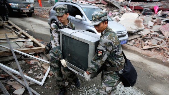 Two soldiers help move a television from a damaged house on Monday in Ya