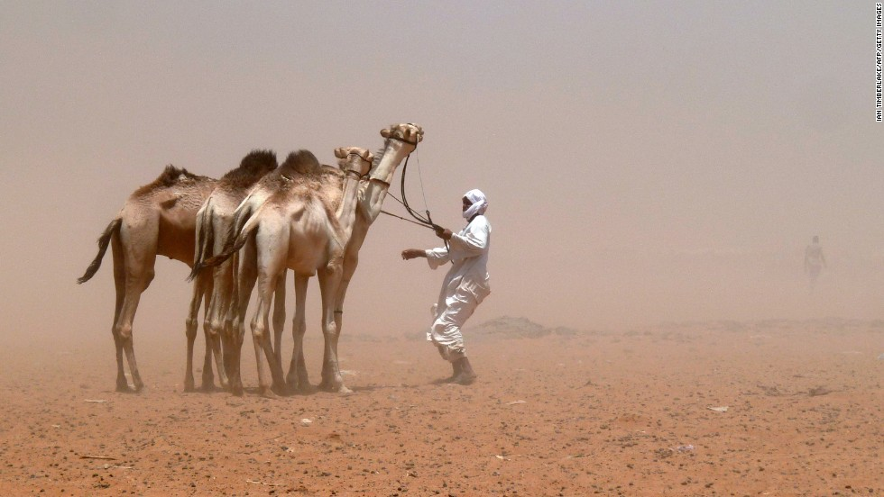 A camel herder guides his animals during a sandstorm on the edge of Khartoum, Sudan, on Saturday, April 20.