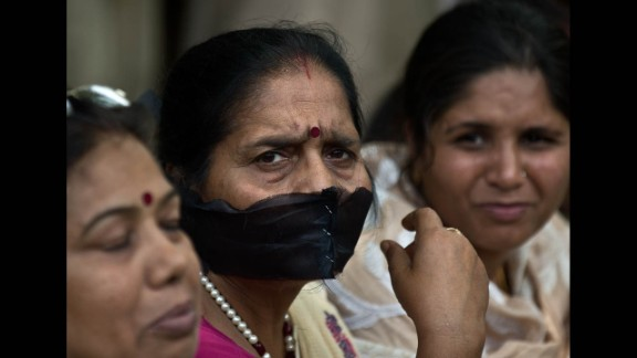 A woman covers her mouth with a black cloth during Tuesday