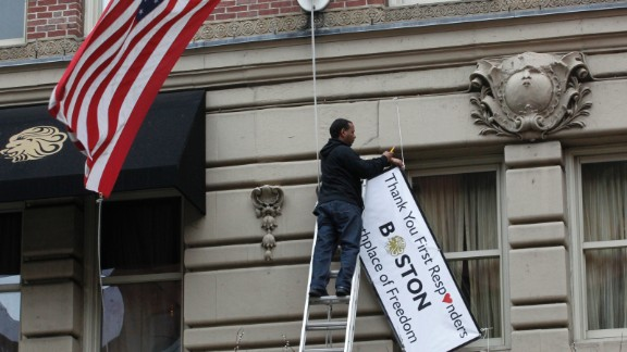 A man removes a sign hanging from the Lennox Hotel along Boylston Street after the street reopened to the public for the first time since the Boston Marathon bombings in Boston on Wednesday, April 24. The city is trying to return to normal less than a week after two bombs exploded near the finish line of the Boston Marathon, shocking the nation and leaving the city on edge. See all photography relating to the Boston bombings.