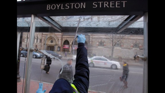 A man washes a bus stop window on Boylston Street on April 24.