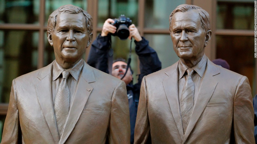 A photographer makes a photo of the two bronze statues of former Presidents George W. Bush and his father, George H.W. Bush, in a courtyard at the Center.