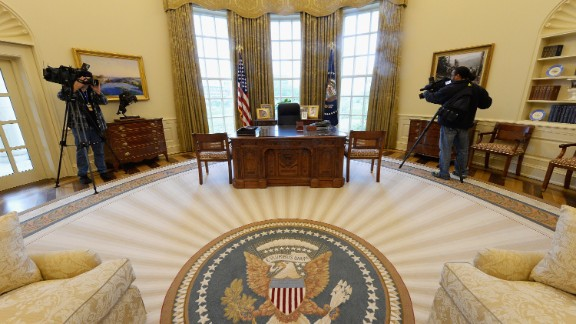 Members of the media shoot video inside a recreated White House Oval Office during a tour of the George W. Bush Presidential Center.