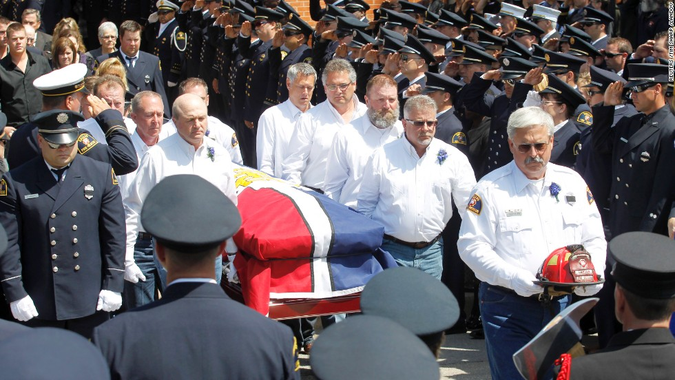 "Pallbearers carry the casket of fallen firefighter Capt. Kenneth ""Luckey"" Harris Jr. after his funeral at St. Mary's Catholic Church of the Assumption in West, Texas, on April 24."