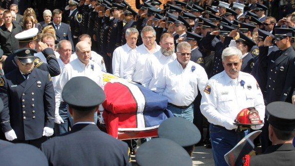 "Pallbearers carry the casket of fallen firefighter Capt. Kenneth ""Luckey"" Harris Jr. after his funeral at St. Mary"