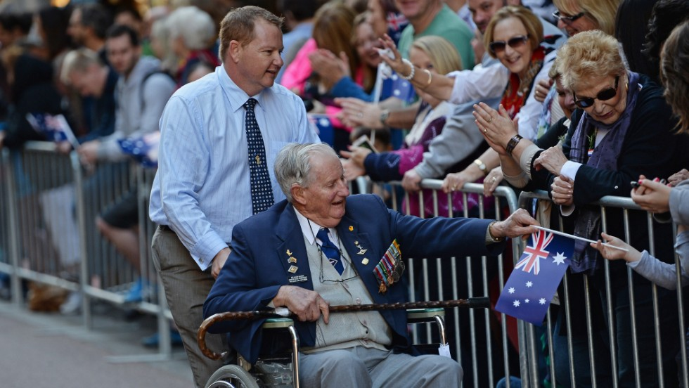 A veteran gives his Australian flag to a spectator during the ANZAC Day parade through Sydney on Thursday.