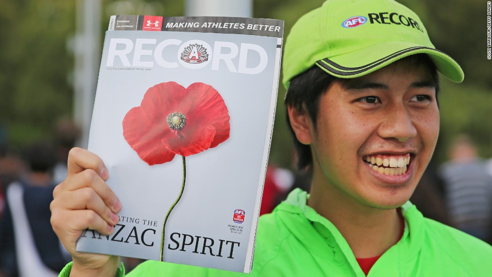 "A salesman holds a copy of ""Record"" magazine before the Australian Football League's ANZAC Day match between the Essendon Bombers and the Collingwood Magpies on Thursday in Melbourne, Australia."