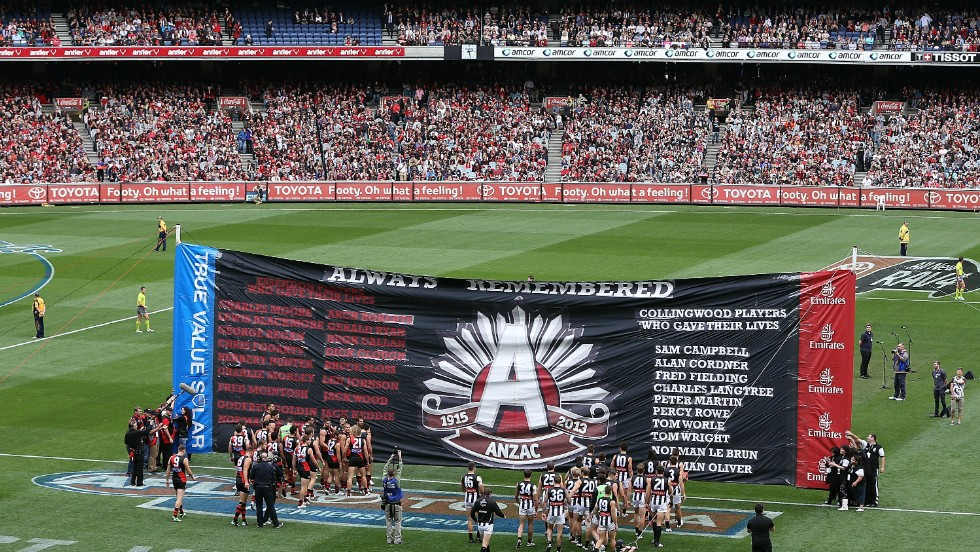 The Essendon Bombers and Collingwood Magpies players walk through the ANZAC Day banner during the round five of their match at the Melbourne Cricket Ground on Thursday.