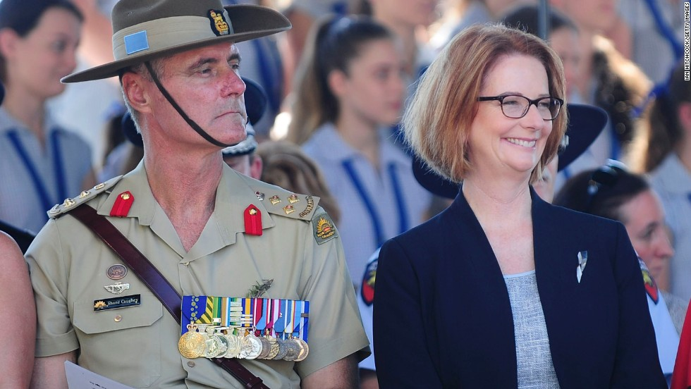 Australian PM Julia Gillard sits with Brigadier Shane Caughey during a commemorative service on Thursday in Townsville, Australia.