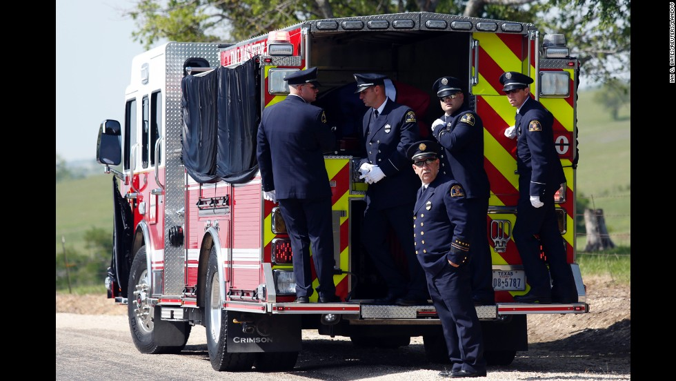 Firefighters stand on the back of a firetruck that transported Harris' body to the Bold Springs Cemetery in West on April 24.