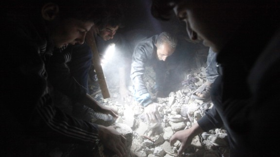 Searchers use a flashlight as they look for  survivors among the rubble created by what activists say was a missile attack from the Syrian regime, in Raqqa province, Syria, on April 25.